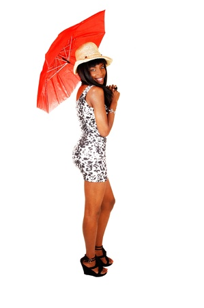 A slim and tall African American woman standing in profile in a short dressfor white background with a red umbrella in her hand and a straw hat onher head  photo