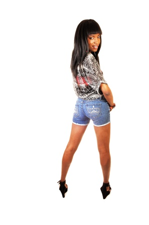 A tall and slim young black woman in a blouse and jeans shorts standingfrom the back on white background, looking over her shoulder  photo
