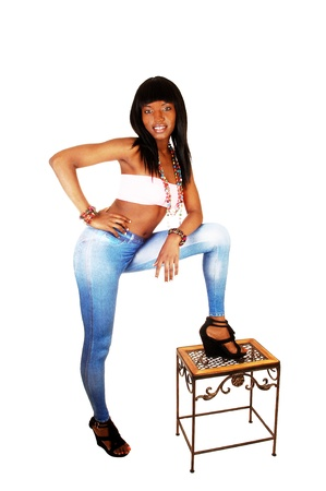 tight fitting: A pretty black woman in blue tights and long black hair standing for whitebackground having one leg on a small bench  Stock Photo