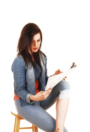 A young pretty woman sitting on a chair in blue thighs and a blue jeans jacket and reading the newspaper for white background Stock Photo - 14626019
