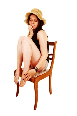 displeased: A young slim woman sitting on a chair with her legs up, wearing a straw hat, looking down in pain for white background  Stock Photo