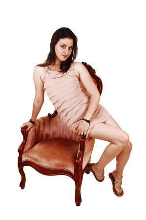アームレスト ピンクの古い椅子、白い背景の上に座って、短いベージュのドレスで美しい若い女性