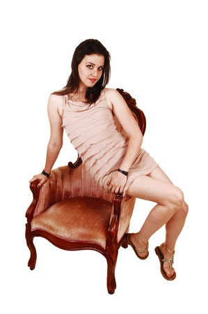 A beautiful young woman in a short beige dress sitting on the armrest ofa pink old chair, for white background