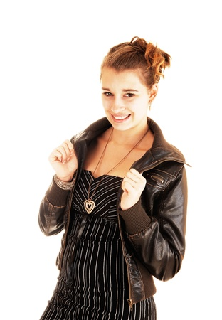 A nice brunette woman in a black striped dress and a brown leather jacketstanding for white background, smiling into the camera