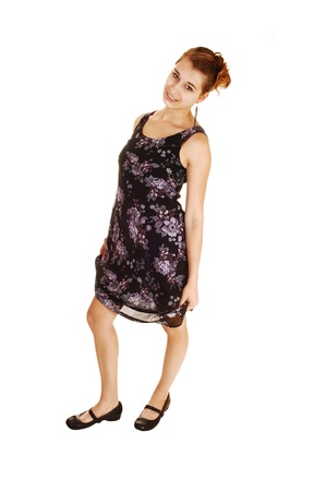 A pretty and young woman in a black dress with flowers on standing fromthe side for white background  photo