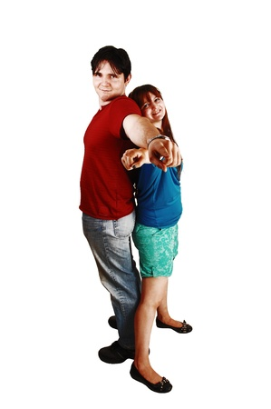 A young couple standing back to back for white background andpointing both with there finger to the camera
