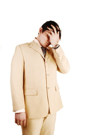 A businessman standing in a beige suit, holding he hand over his face,is ashamed over his bankrupts, over white background  photo