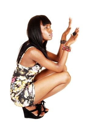 For white background a pretty African American woman crouching onthe floor in a short dress, heels and with her long black hair  photo