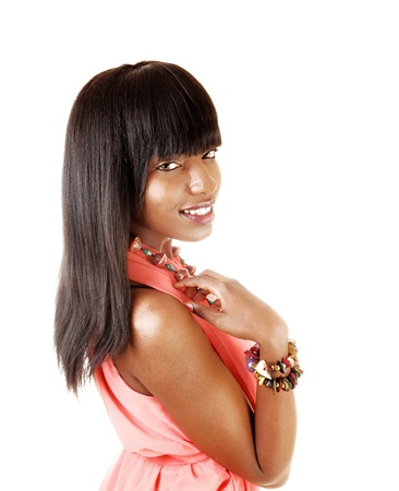 A portrait shoot of young African American woman in profile, with her long black hair in a pink dress for white background  photo