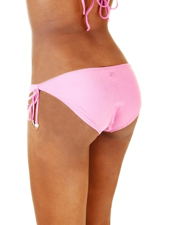 The nice round butt of a young African American woman with a perfectfigure in a pink bikini panties, for white background  photo
