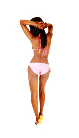 A pretty young African American woman with a perfect body from theback in a pink bikini and heels, standing from the back for white background