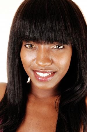 Een close-up foto shoot van een mooie Afrikaanse Amerikaanse vrouw met Herlong zwart steil haar, glimlachend voor een witte achtergrond