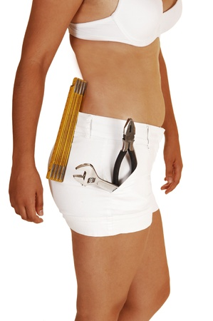 A young slim woman in white shorts and a white bra with some tools inher shorts, planning to do some repair in her home, for white background  photo
