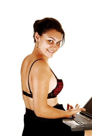 A pretty and friendly young woman sitting on a chair with a laptop on herlap, in a black skirt, high heels and a black and red bra, over white photo