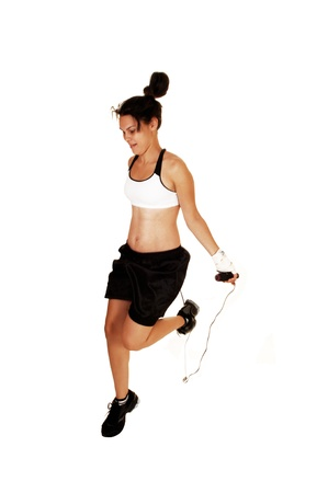 A young woman in a sports bra and black boxer shorts is training with ajump-rope for her next boxing fight, for white background  Stock Photo