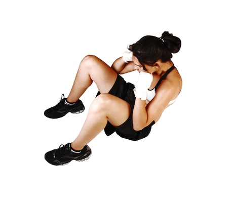 working woman: A young woman preparing for a boxing much with hard training, sittingon the floor and doing many sit-ups, for white background