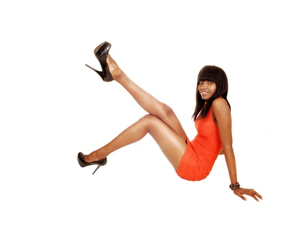 A pretty black girl sitting on the floor, lifting up her leg and having fun,for white background  photo