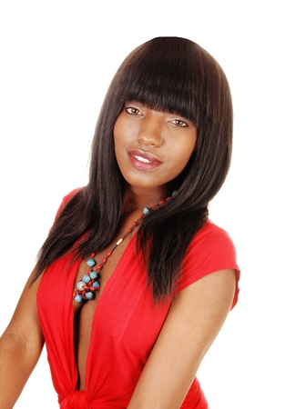 A beautiful young black woman in a red blouse and long black hairsitting for white background and looking into the camera