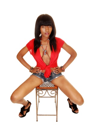 Een zeer slanke jonge zwarte vrouw zitten in een rode blouse en jeans shortson een bankje met haar lang zwart haar voor witte achtergrond