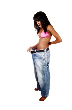 A pretty African American woman in a pink bikini put on her old jeansand find out she lost a lot of weight, for white background  photo