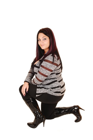 A lovely young woman in a gray black sweater, black tights and bootskneeling for white background in the studio  photo