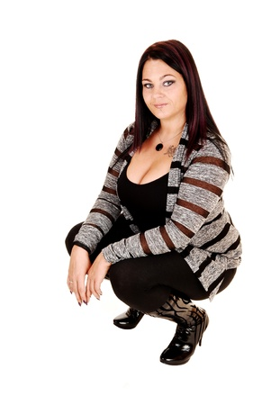 A pretty woman in a gray black sweater black top and tights and bootscrouching in the floor in the studio for white background  photo