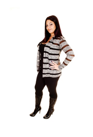 A young woman in a black sweater, black tights and boots standing forwhite background in the studio, looking into the camera  photo
