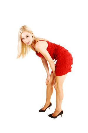 bending down: Una mujer rubia hermosa y alta de pie en un vestido rojo y zapatos de tac�n alto enel estudio para el fondo blanco y doblado hacia abajo Foto de archivo
