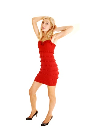 A lovely slim young woman standing for white background in a red dressand black high heels with her hands behind her head  photo