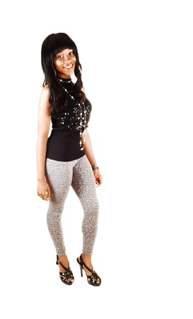 A very pretty African American young woman in gray tights and a blacksweater and long curly black hair standing for white background  photo