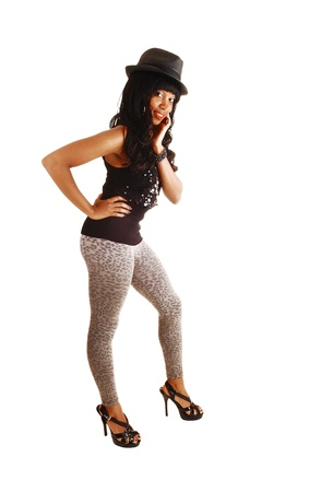 An elegant African American woman in gray tights, a black sweater anda hat standing with her long black curly hair for white background  photo