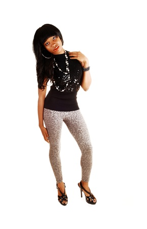 A lovely African American woman in her twenties standing for white background in gray tights and a black sweater on high heels  photo