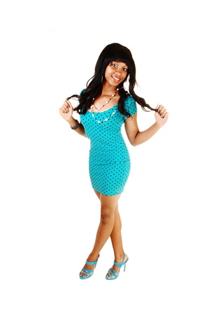 A lovely African American young woman in a turquoise dress and highheels playing with her nice long curly black hair for white background  photo