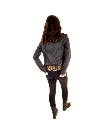 A young woman standing in the studio in a black leather jacket and bootswith long brunette hair and jeans for white background  Banque d'images