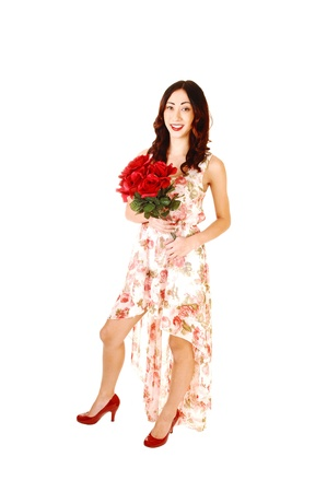 A pretty young woman in a evening dress, long in the back short in thefront, with a bunch of red roses, for white background  photo