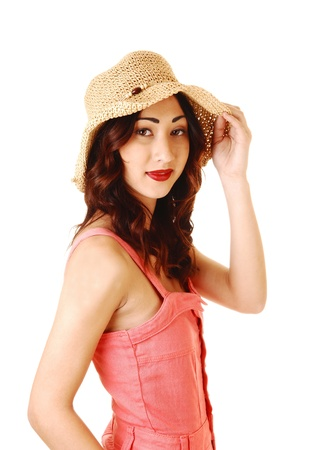 A pretty woman in a pink dress wearing a straw hat, with long brunettehair, in portrait shoot for white background  photo