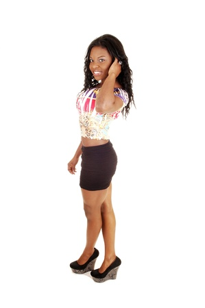 A slim young black woman standing in the studio for white backgroundin a short black skirt and colorful blouse showing her nice figure  photo