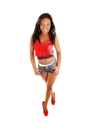 A lovely black woman in jeans shorts and red blouse standing for whitebackground in red high heels and smiling, with her long black hair  photo