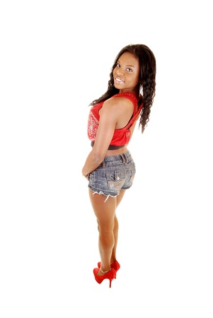 A young pretty black woman in jeans shorts and red top standing from theback for white background, in red heels and smiling  photo