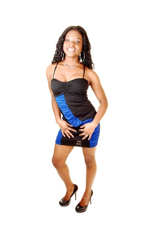 A pretty young smiling black woman standing for white background in ablack and blue evening dress and high heels, smiling  photo