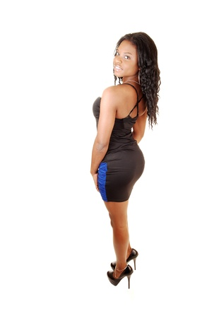 A nice figured young black woman standing for white background in the studio in a black and blue dress, with her long black hair  photo