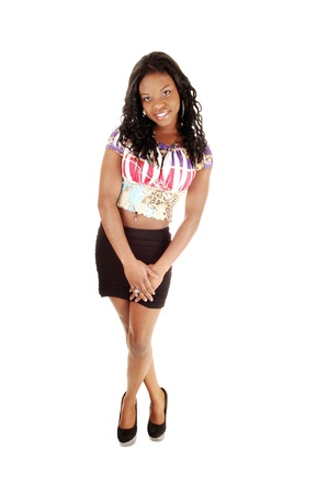 A gorgeous young black girl standing for white background in a blackskirt and blouse, smiling with her long black hair