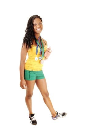 A young pretty black girl in green shorts and a yellow top standing for whitebackground, showing her 4 medals from a sprinting competition  photo
