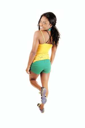 A lovely smiling black woman in green shorts and yellow tank top standingfrom the back, looking over her shoulder, for white background  photo