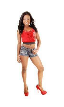 A black woman in jeans shorts and a red tank top and red heels, standingfor white background, smiling, with her long black hair