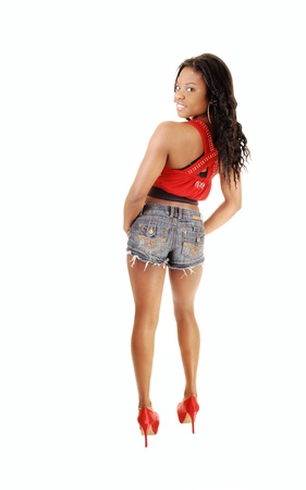 A smiling young woman standing in jeans shorts and red tank top from theback, in high heels, with her long black hair, for white background  photo