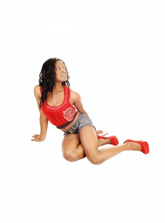 tanktop: A beautiful black woman sitting on the floor in jeans shorts and a red tanktop, looking up for white background