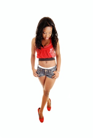 A pretty black woman in jeans shorts and a red tank top and heels, standingfor white background, looking down  photo