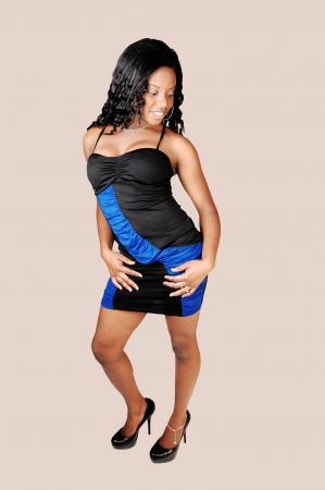 A sexy young black woman standing for light gray background in a black andblue evening dress, looking down wards and smiling Stock Photo - 16520074