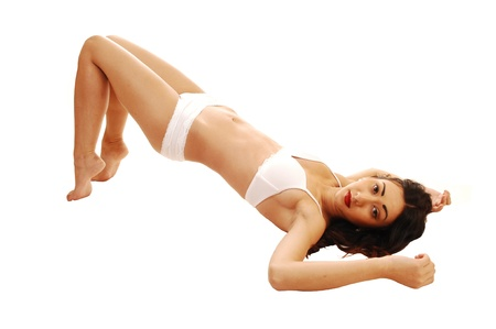 A slim young woman in white underwear lying on the floor, lifting her butt up, for white background  photo